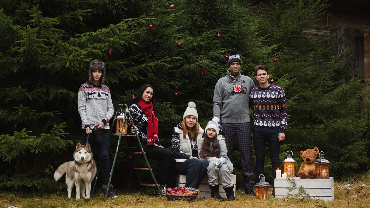 A family of six stands outside in sweaters.